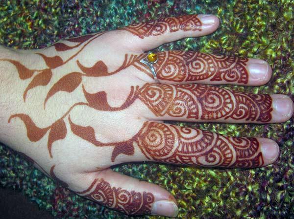 finger mehendi design of swirls and darkened leaves