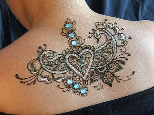 heart and peacocks Mehandi design on back of women
