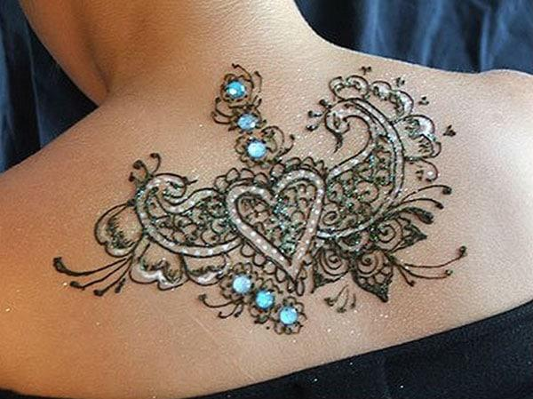 heart and peacocks Mehandi design on back of women