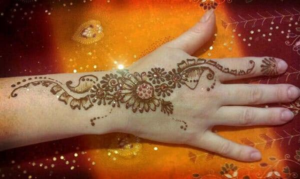 floral Mehandi design on back hand for an ornate look