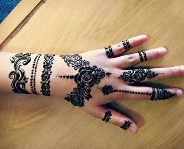 A marvelous rose henna design on back hand for girls