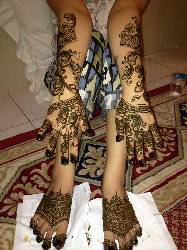 Flower and spirals hand and leg mehendi design for brides