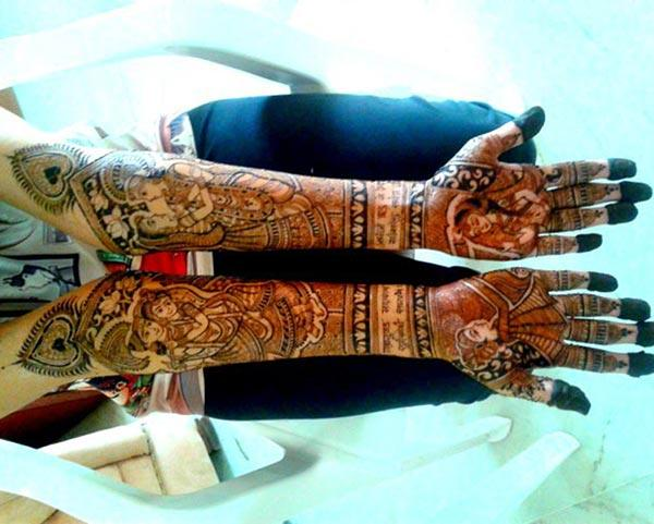 A mind blowing Krishna-Radha mehendi design on full hand for brides