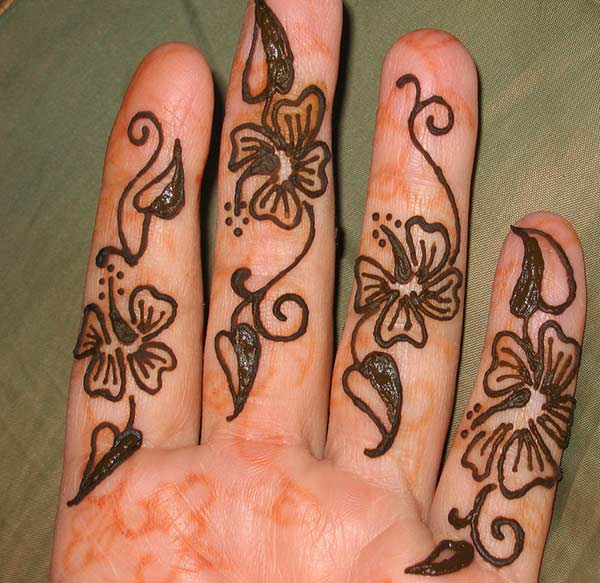 A floral stamping on fingers for women using mehndi designs