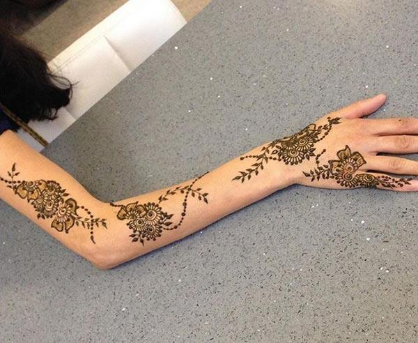 The floral cluster mehendi design on full arm for ladies and girls